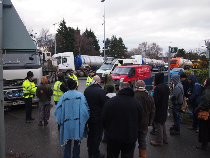 A hotly contested source of energy: Trucks, police and protestors gathering at the entrance to the private road, also a public footpath, where the Barton Moss exploration site was situated. The protestors have staged daily protests, Monday – Friday, by walking in front of lorries and vehicles entering and leaving the site. Vehicles would arrive in convoy. Photo taken January 2014 by Craig Thomas.